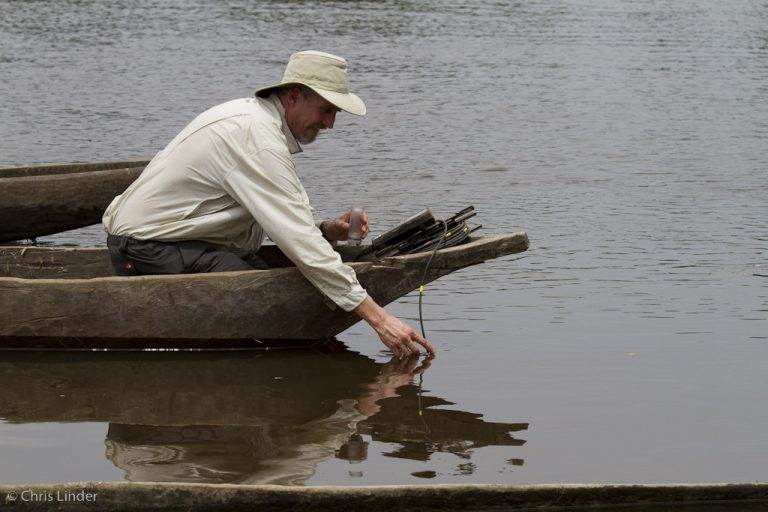 Dr. Max Holmes taking water samples from wooden canoe.