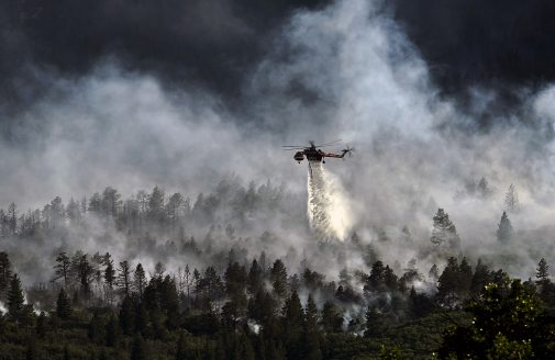 Stock image of helicopter dropping water on a forest fire.