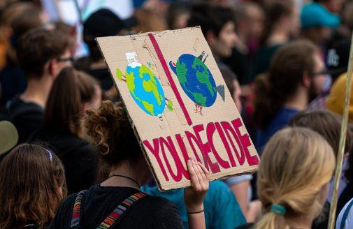"Climate activism demonstration sign reading ""you decide."""