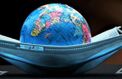 Miniature globe laying inside medical face mask.