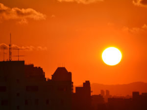 Image of setting sun in a hot-looking orange sky over a city.