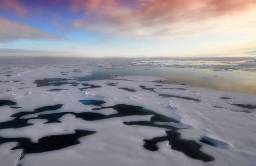 Sunset on partially melted Arctic sea ice