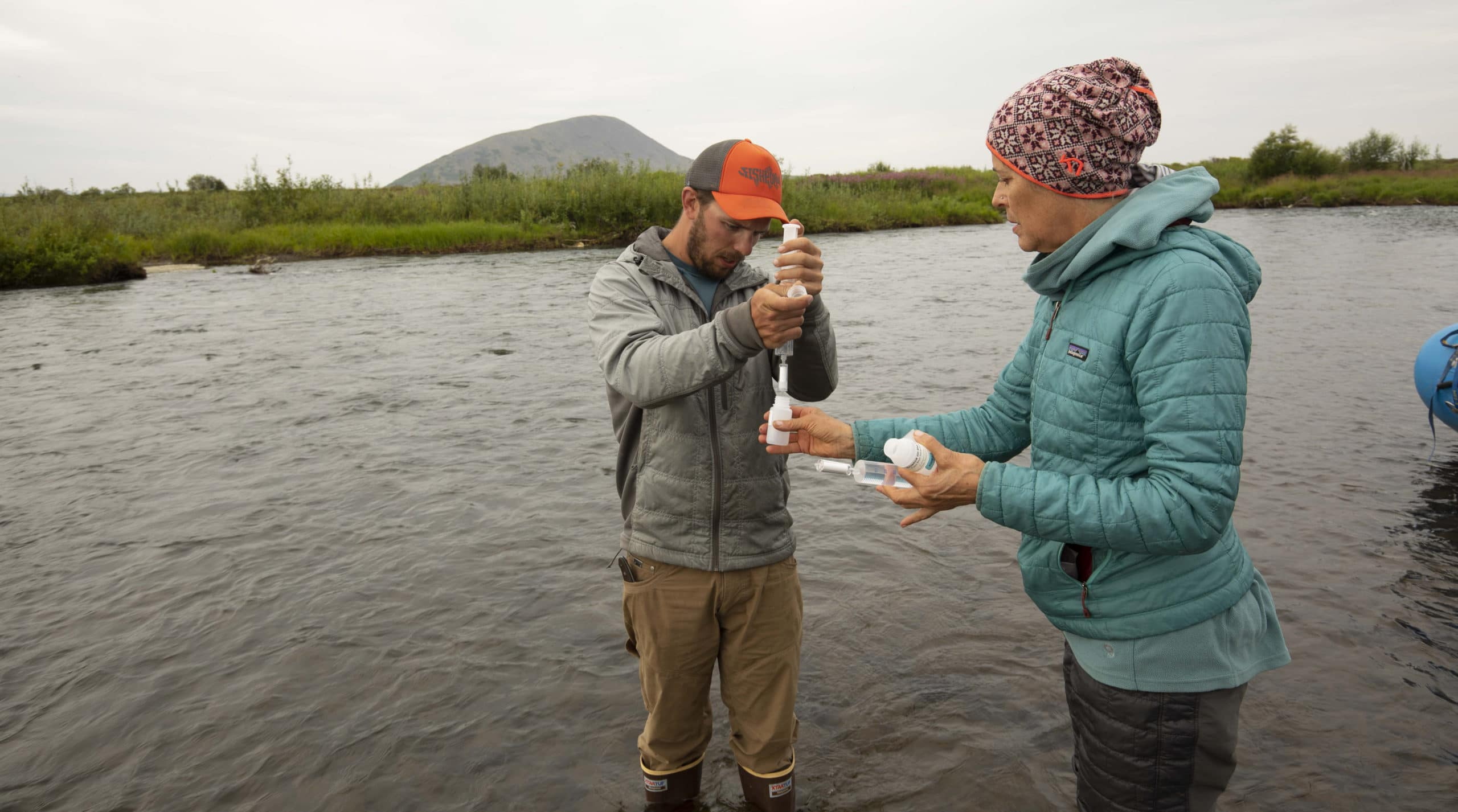two scientists take river water samples